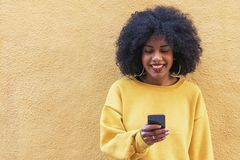 使用机动性的美丽的美国黑人的妇女在街道 免版税库存图片