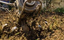 使用机器小店耕地机的农夫为耕的土壤 图库摄影