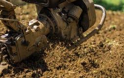 使用机器小店耕地机的农夫为耕的土壤 库存图片