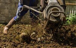 使用机器小店耕地机的农夫为耕的土壤 库存照片