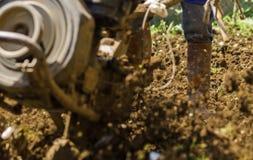 使用机器小店耕地机的农夫为耕的土壤 免版税库存图片