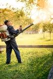 使用机器的产业工人为有机杀虫剂发行在果树园 库存照片