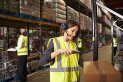 使用条形码读者的妇女在配给物仓库 免版税库存图片