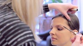 使用染睫毛油的化妆师在与模型的构成一起使用 股票视频