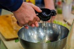 使用柠檬剥削者的人的手对在金属碗的汁液柠檬 库存照片