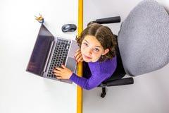 使用查寻的膝上型计算机的年轻白种人女孩研究 从上面被射击的演播室 库存图片