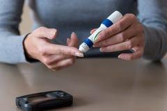 使用柳叶刀的妇女手在检查血糖水平的手指 免版税库存照片