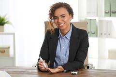 使用柳叶刀笔的年轻非裔美国人的妇女在工作场所 库存照片