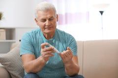 使用柳叶刀笔的老人在家 免版税图库摄影