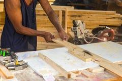 使用桌的资深男性木匠为切开木头看见了在worksh 库存图片