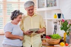 使用桌计算机的亚洲资深夫妇对在家搜寻菜单菜的食谱和类型在厨房里 资深与技术 库存照片