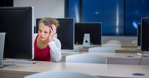 使用桌面computer/pc的俏丽,年轻女性大学生 免版税库存图片