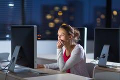 使用桌面computer/pc的俏丽,年轻女性大学生 免版税图库摄影