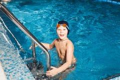 使用梯子的年轻男孩退出游泳池 图库摄影
