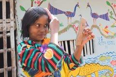 使用梳子和玻璃的女孩在Pingla,西孟加拉邦,印度调直头发 免版税库存照片