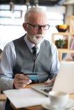 使用检查的膝上型计算机的资深商人信用卡 免版税图库摄影