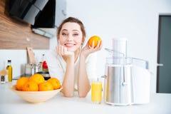 使用榨汁器的美丽的妇女为做橙汁 免版税图库摄影
