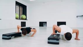 使用步平台,一个男人和一名妇女在健身演播室做俯卧撑 股票视频