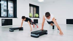 使用步平台,一个男人和一名妇女在健身演播室做俯卧撑 股票录像