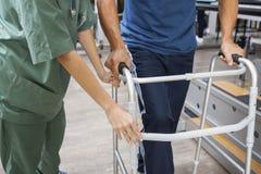 使用步行者,协助老人的护士的中央部位走 免版税库存照片