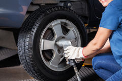 使用气动力学的板钳的女性技工修理汽车 免版税库存图片