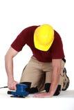 使用沙磨机的建造者在地板上 免版税库存图片