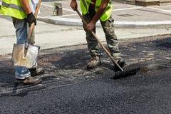 使用沥青摊铺机工具的工作者在修路时 免版税库存图片