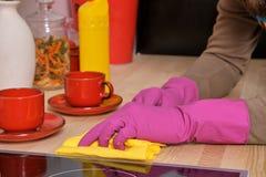 使用洗涤剂,年轻英俊的有胡子的人在厨房、佩带的围裙和桃红色手套里清洗烹调表面 库存图片