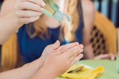 使用洗涤的母亲和儿子递在咖啡馆的消毒剂胶凝体 免版税库存图片