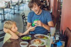 使用洗涤的父亲和儿子在吃递消毒剂胶凝体在咖啡馆前 免版税库存照片