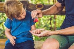 使用洗涤的父亲和儿子在快餐前递消毒剂胶凝体在公园 库存照片