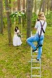 使用活梯的专业婚礼摄影师做图片新娘 免版税库存图片