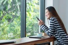 使用流动听的音乐的愉快的亚洲妇女在窗口附近在caf 库存图片