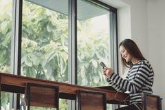 使用流动听的音乐的愉快的亚洲妇女在窗口附近在caf 图库摄影