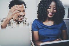 使用流动小配件的微笑的有吸引力的非裔美国人的夫妇在家,当坐沙发时 水平,弄脏 免版税库存照片