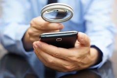 使用流动巧妙的电话的商人有放大镜的 Pho 库存照片