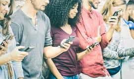 使用流动巧妙的电话的多文化朋友小组 免版税库存照片
