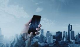 使用流动巧妙的电话的手有两次曝光现代城市背景,通信和网络连接技术 库存图片