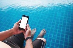 使用流动巧妙的电话,在屏幕上的空白的一个人,当腿浸洗在水池在夏天 在手机屏幕上的裁减路线 免版税库存图片