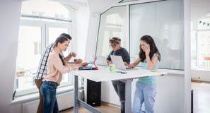 使用流动技术的繁忙的工友,当分享书桌在工作插孔时 图库摄影