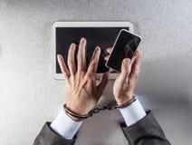 使用流动技术,工作狂商人栓了对通信手铐 免版税库存照片