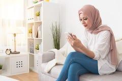使用流动智能手机的典雅的女性穆斯林 库存图片