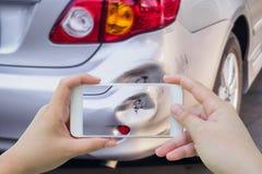 使用流动智能手机的妇女拍车祸照片  免版税图库摄影