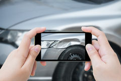 使用流动智能手机的妇女采取照片车祸事故 库存照片