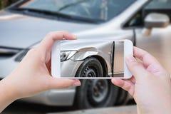 使用流动智能手机的妇女采取照片车祸事故 免版税库存图片
