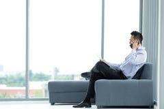 使用流动智能手机的年轻亚洲商人坐沙发 免版税库存图片