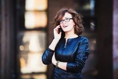 使用流动智能手机的微笑的少妇 免版税库存照片