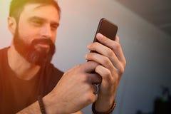 使用流动智能手机的确信的有胡子的人在办公室 被弄脏的背景 火光 图库摄影