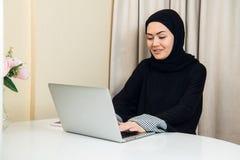 使用流动膝上型计算机的典雅的可爱的回教妇女在家搜寻网络购物信息在客厅 库存图片