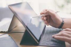 使用流动触感衰减器的博客作者为工作 男性手特写镜头视图使用铁笔笔的感人的电子片剂屏幕的 免版税库存图片